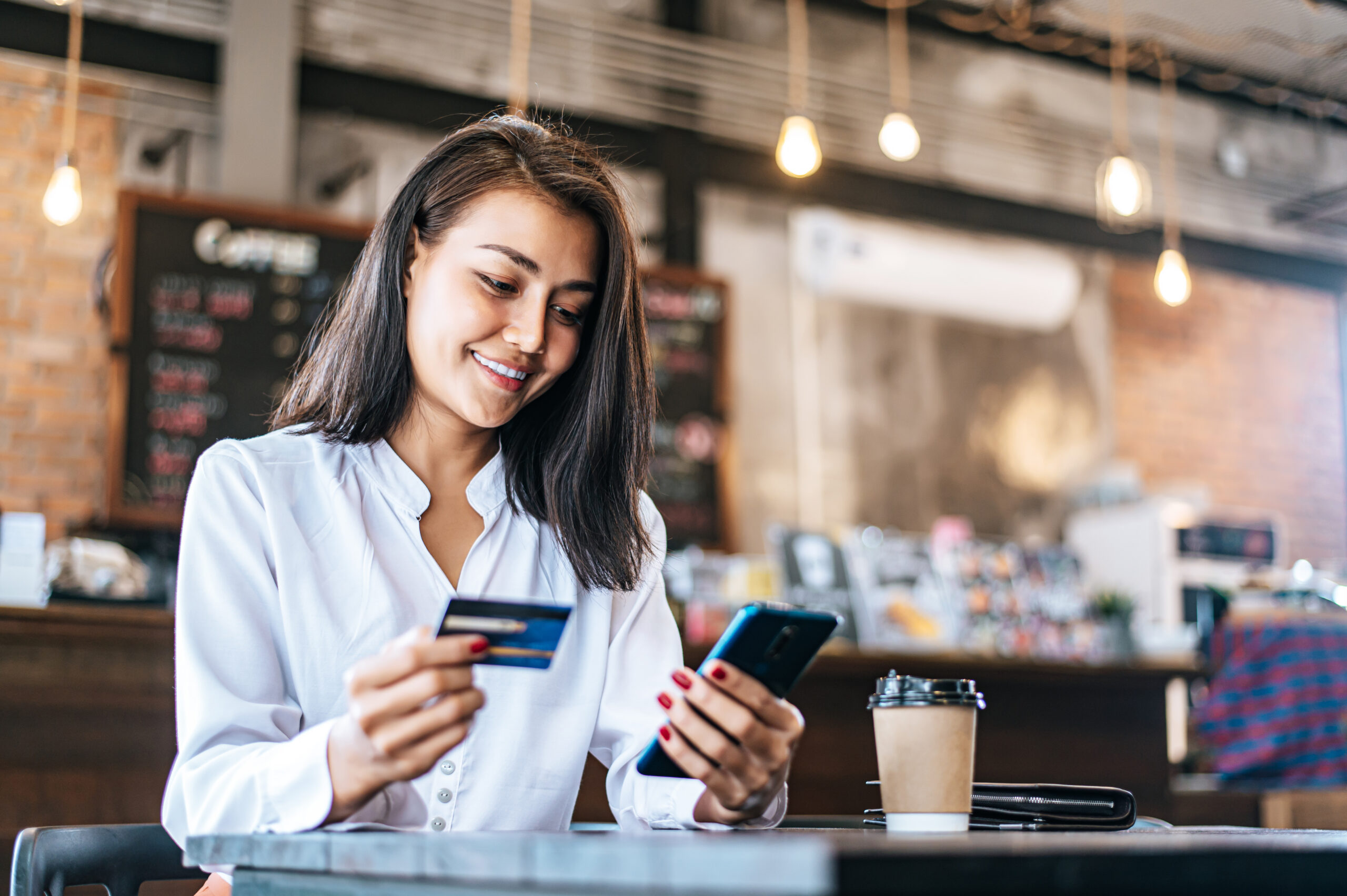 woman at cafe using credit card for mobile commerce